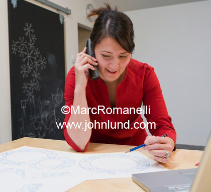Asian American businesswoman in a red blouse talking on the phone.  She has a pencil in her hand and is looking at some kind of blue prints or documents.